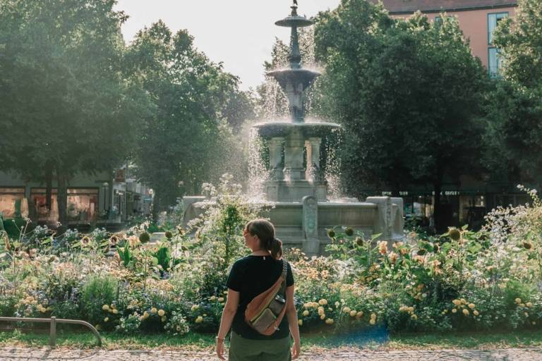 Eine Frau steht vor einem Brunnen am Weißenburgerplatz in München