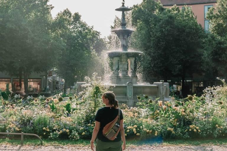 A woman is standing in front of a fountain on Weißenburgerplatz in Munich