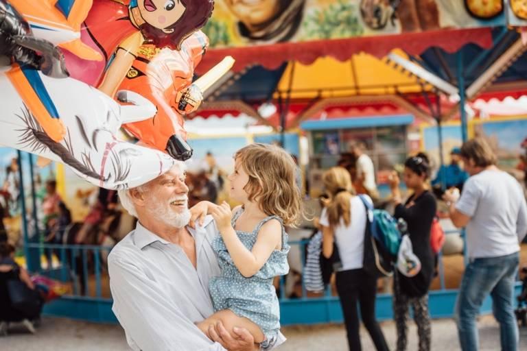 Ein älterer Mann mit kleinem Kind auf der Auer Dult in München.
