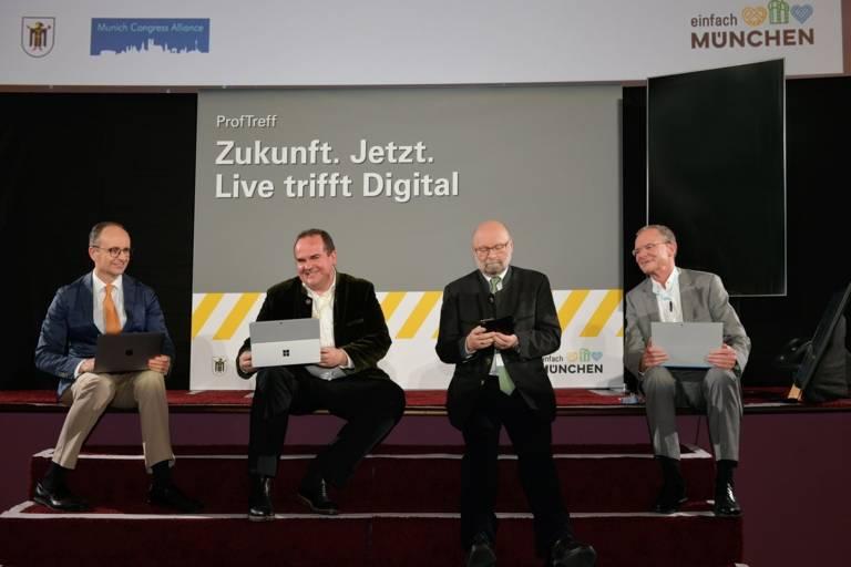 Vier Personen sitzen auf einer Bühne.