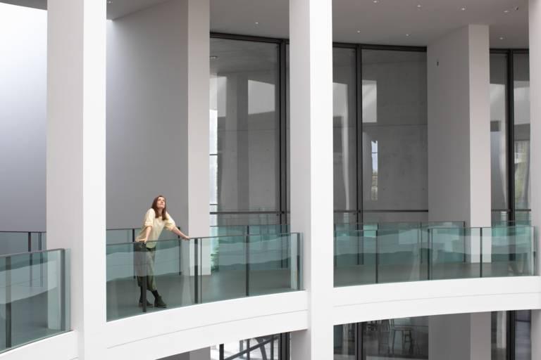 Eine junge Frau steht in einem leeren Museum in München.
