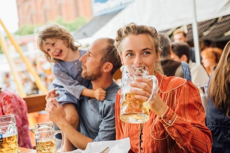 Eine Frau trinkt eine Mass Bier auf der Auer Dult in München