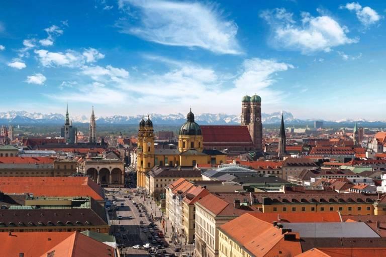 Blick über die Dächer Münchens mit Alpenpanorama im Hintergrund.