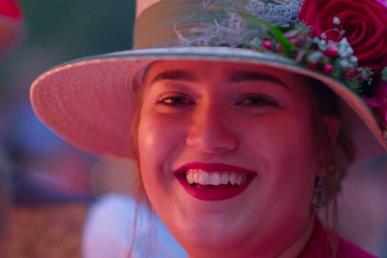 A smiling young woman with a hat at the Kocherlball in Munich
