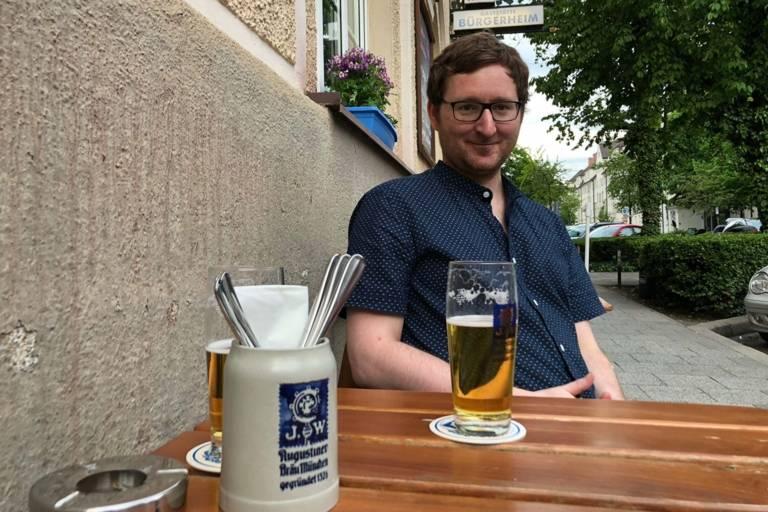 Mann mit Bier vor einem Gasthaus in München.