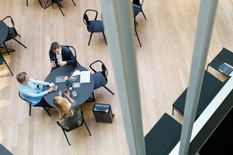 Zwei Frauen und ein Mann sitzen an einem Tisch im Foyer eines Hotels in München.