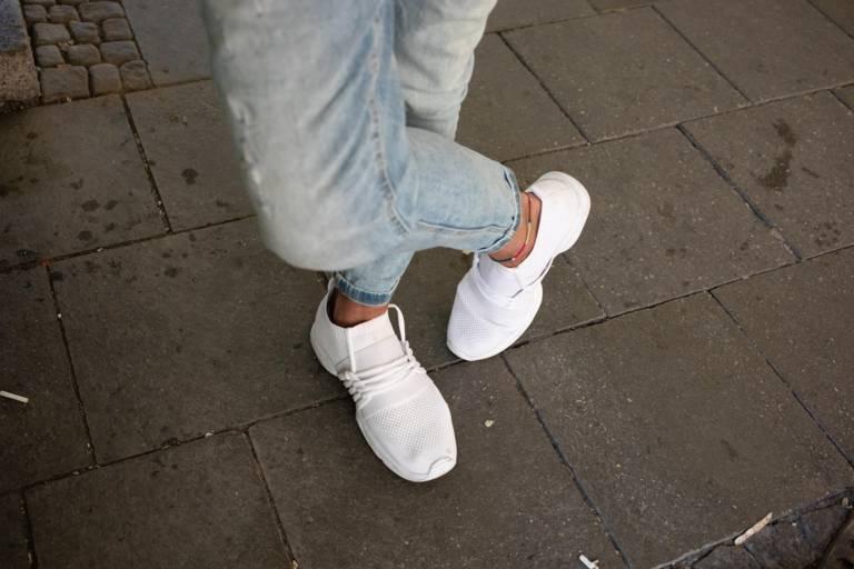 Jeans und weiße Sneaker eines Mann in München.