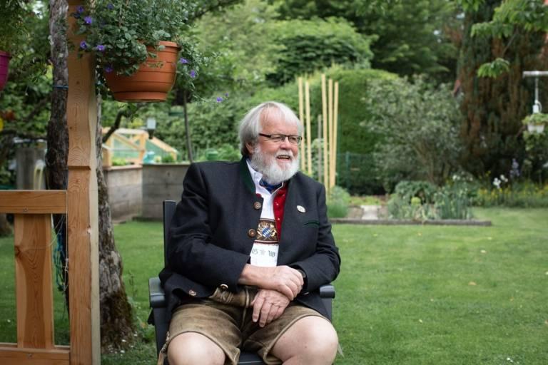 Günter Werner sitzt in einem Garten bei München