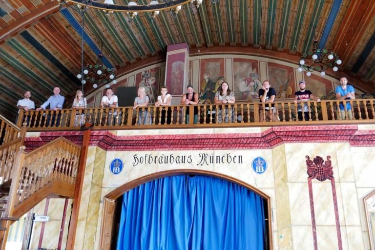 Die neuen Rikschaguides auf einer Empore im Hofbräuhaus in München