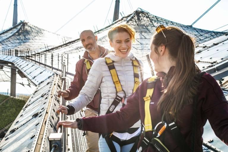 Zwei Frauen und ein Mann stehen auf dem Dach des Olympiastadions in München.