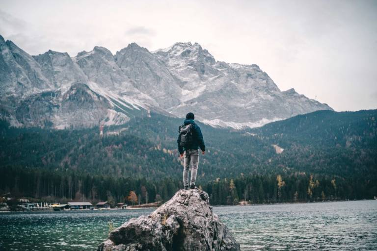 A man is standing on rocks at the shore of Eibsee nearby Garmisch in the surrounding region of Munich.