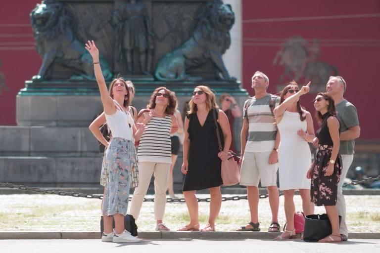 Eine Gästeführerin weist eine Gruppe von Besucher*innnen mit ausgestreckter Hand auf ein besonderes Detail hin.