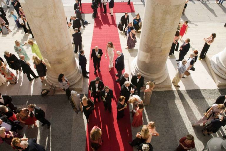 People on a red carpet at the entrance of the Bavarian State Opera during the Opera Festivals in Munich.