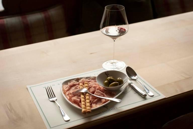 Ein Glas Wein und ein Teller Schinken und Oliven in Geisels Vinothek in München