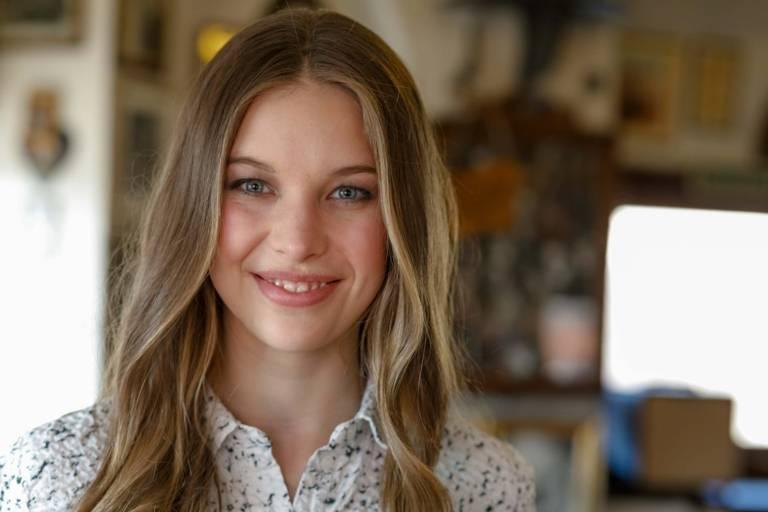 Eine junge Frau steht im Valentin-Karlstadt-Musäum in München und lächelt in die Kamera.
